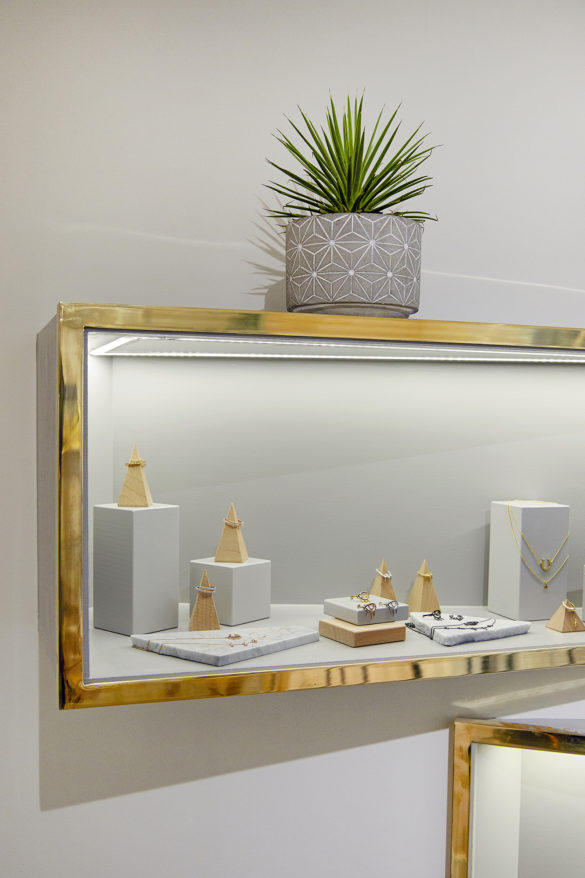 House of Sylphina commercial interior design for Astrid and Miyu flagship, London. Gold trim shelving with plant detail.