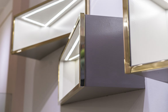 House of Sylphina commercial interior design for Astrid and Miyu flagship, London. Purple shelving with gold trim.